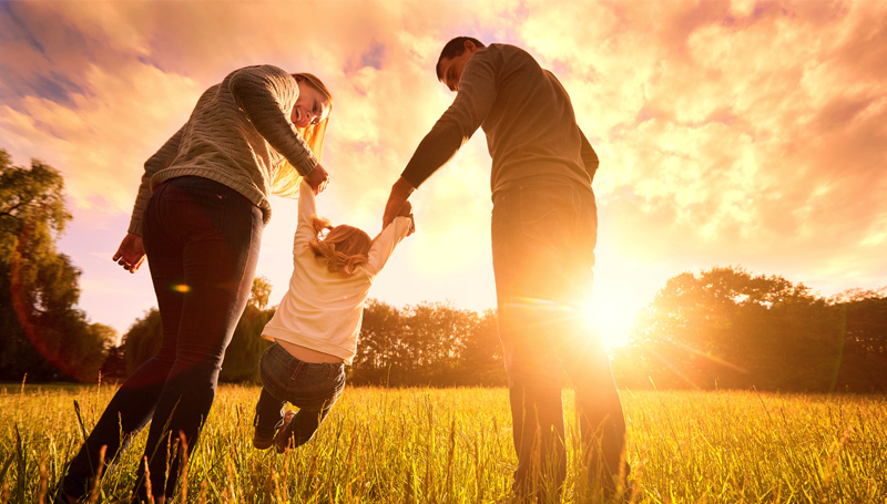 parents-swinging-adoptive-child-in-field