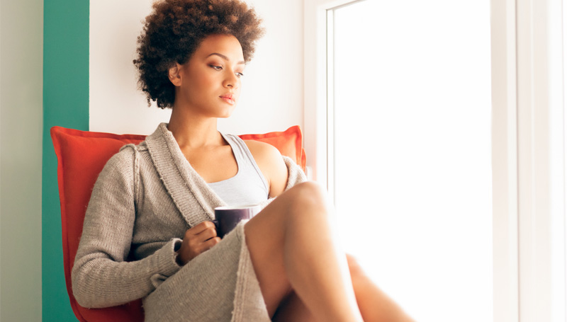 young woman sitting alone thinking