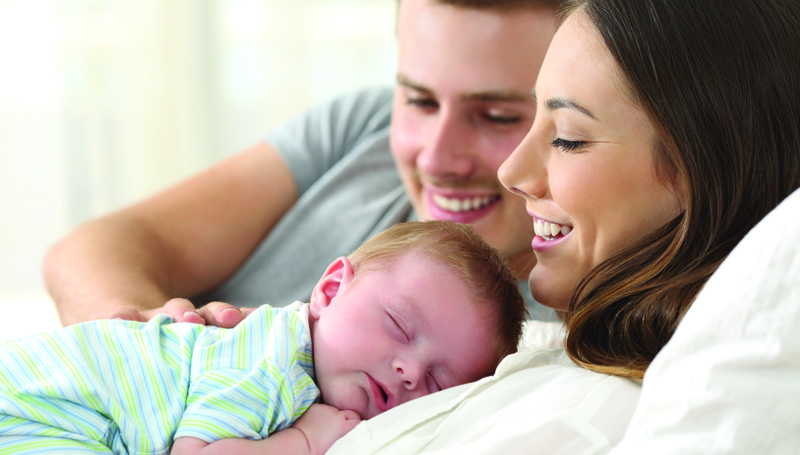 happy mom dad and baby snuggling