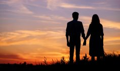 couple holding hands silhouetted against the sunset