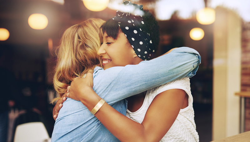 female friends hugging in a coffee shop
