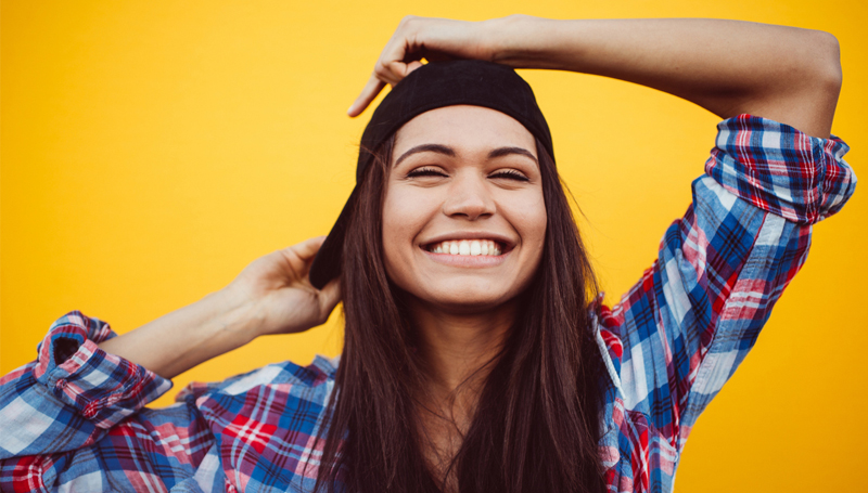 happy young hispanic woman in casual clothes and cap