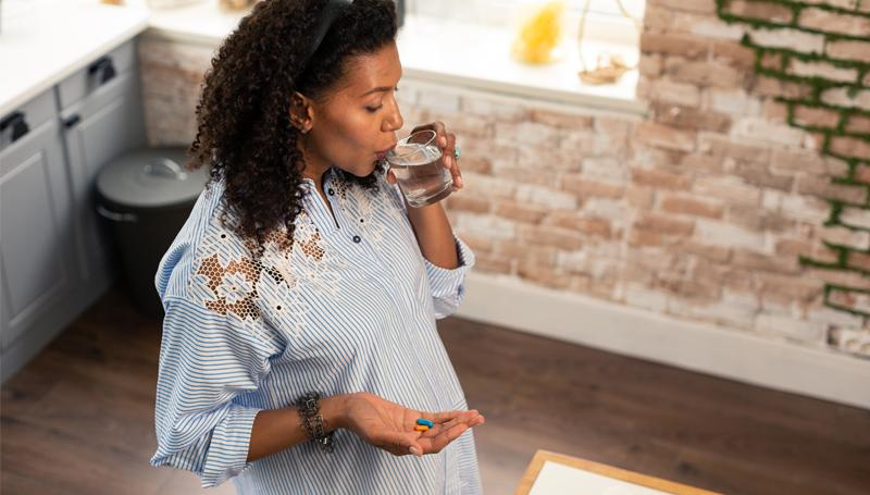 pregnant woman taking prenatal vitamins